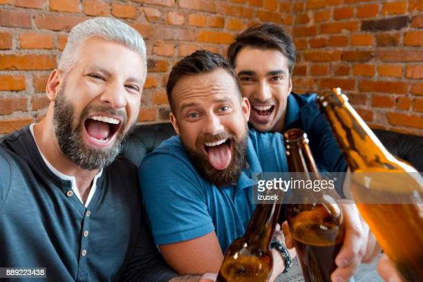 Three friends enjoying at pub and taking selfie