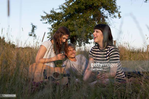 Three friends enjoying sitting in secluded field with wine and guitar