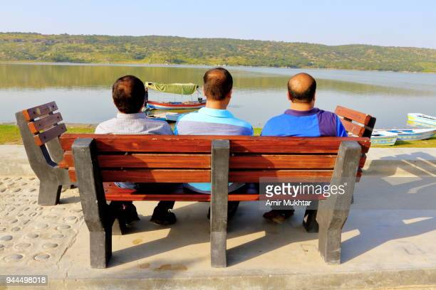 Three friends enjoying the nature looking at the lake while sitting on the bench