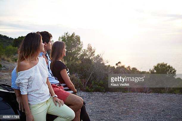 three friends enjoying the sunset over the ocean - klaus vedfelt mallorca stock pictures, royalty-free photos & images