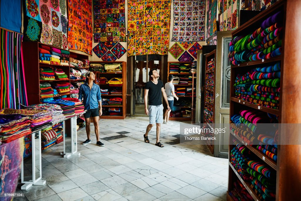 Three friends exploring local market filled with blankets and quilts : Stock Photo