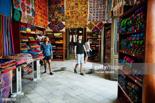 Three friends exploring local market filled with blankets and quilts