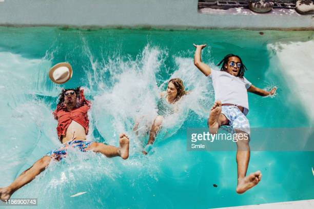 three friends falling backwards into swimming pool - pool party stock pictures, royalty-free photos & images