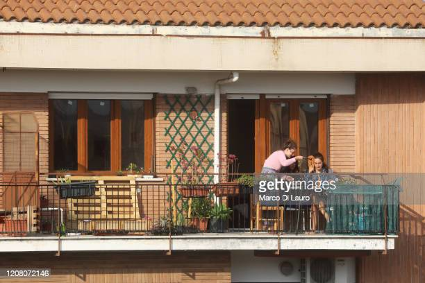 Three friends have lunch with spaghetti on their balcony on March 22 2020 in Rome Italy As Italy extends its nationwide lockdown to control the...