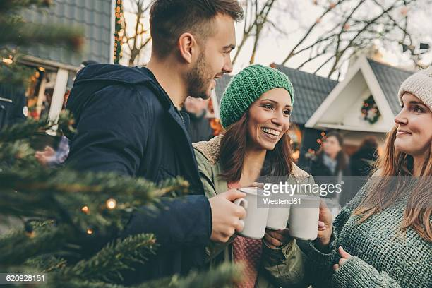 Three friends having a hot punch on the Christmas Market