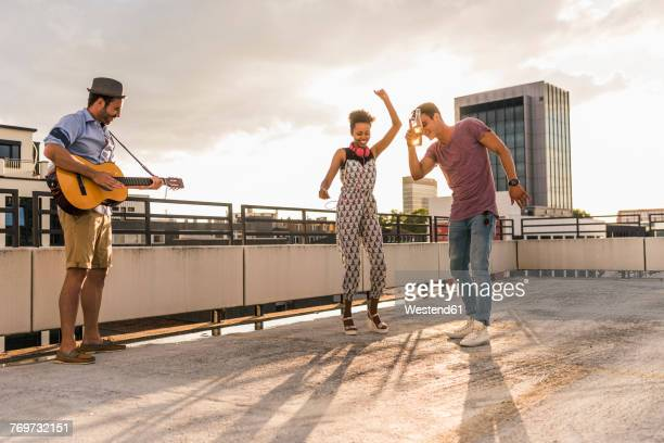 three friends having a rooftop party - plucking an instrument stock pictures, royalty-free photos & images