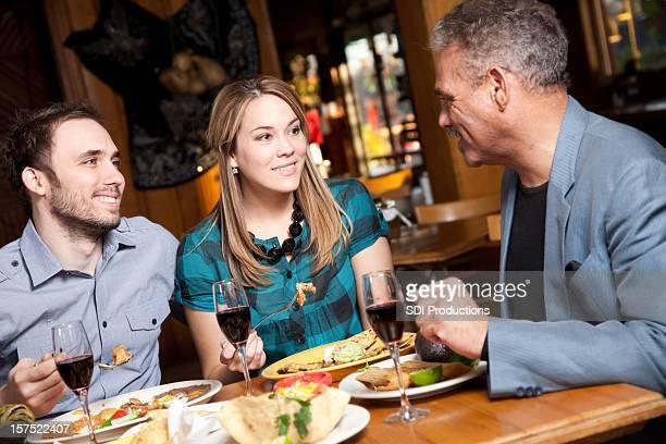 Trois amis ayant un dîner ensemble dans un Restaurant de cuisine mexicaine