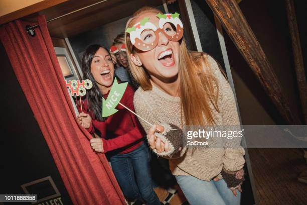 three friends having fun in a photo booth - only mid adult women stock pictures, royalty-free photos & images