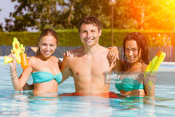 Three friends having fun on swimming pool with squirt guns