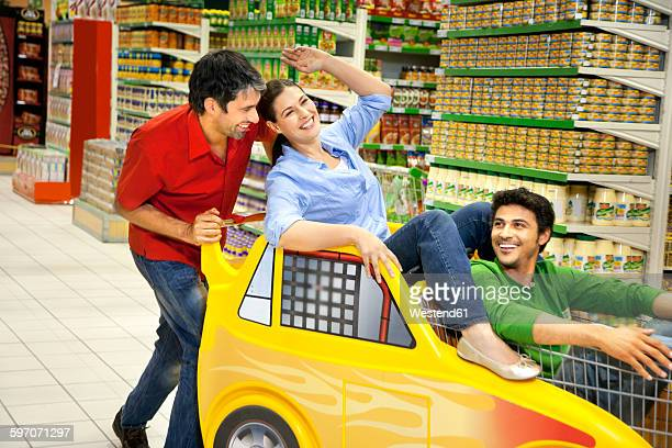 Three friends having fun together in a supermarket