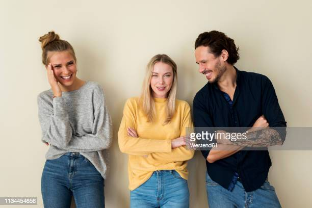 three friends in front of a yellow wall, having fun - drei personen stock-fotos und bilder