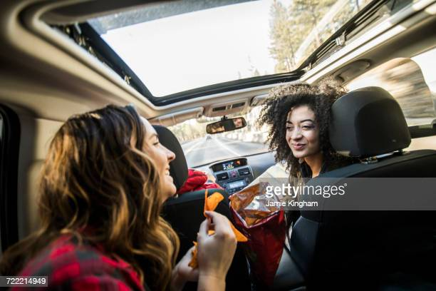 three friends in moving car, two friends sharing crisps - snack stock pictures, royalty-free photos & images