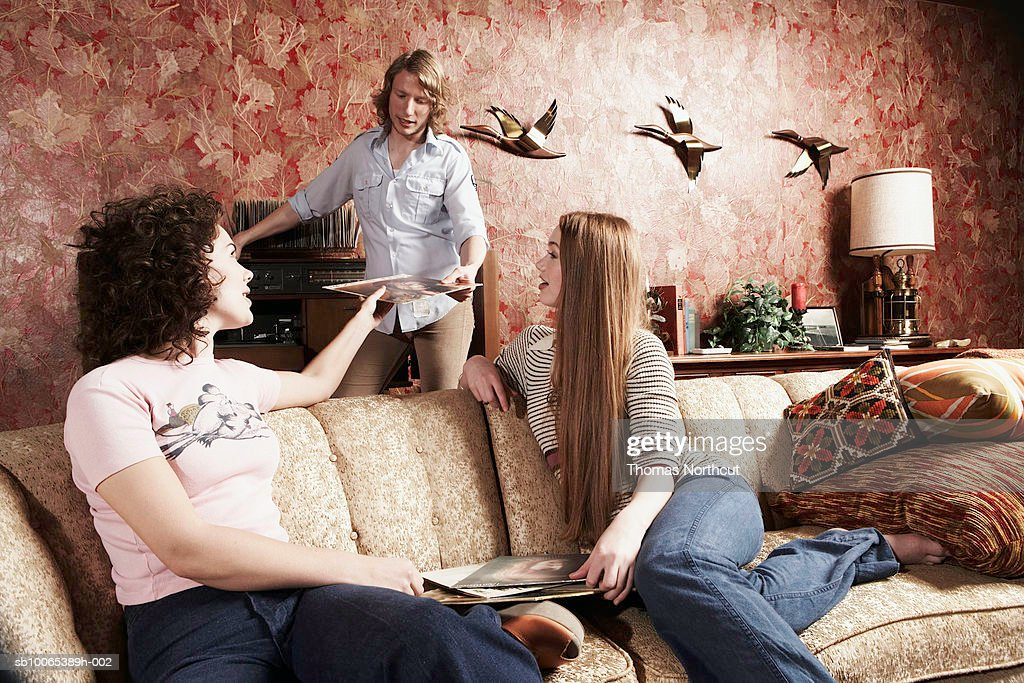 Three friends in room, choosing records : Stock Photo