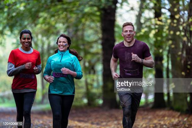 three friends jogging together in country park - small group of people stock pictures, royalty-free photos & images