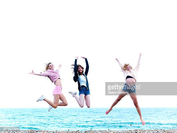 Three friends jumping in excitement on the beach