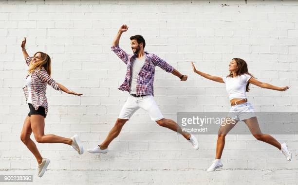 three friends jumping mid-air in front of white wall - hovering stock pictures, royalty-free photos & images