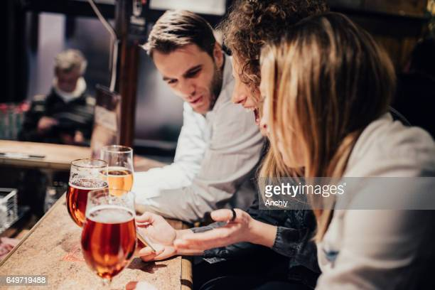 Three friends laughing and drinking beer in a bar