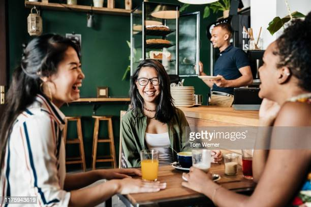 three friends laughing at chatting in coffee shop - zuidoost aziatische etniciteit stockfoto's en -beelden