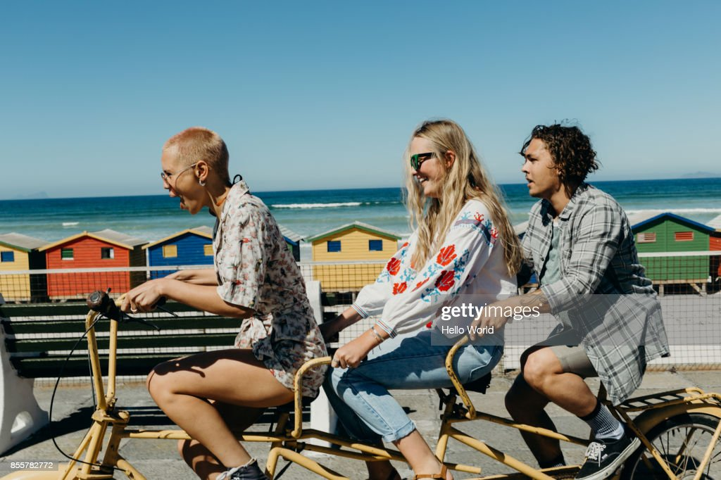 Three friends laughing on a tandem bicycle on a boardwalk : Stock Photo
