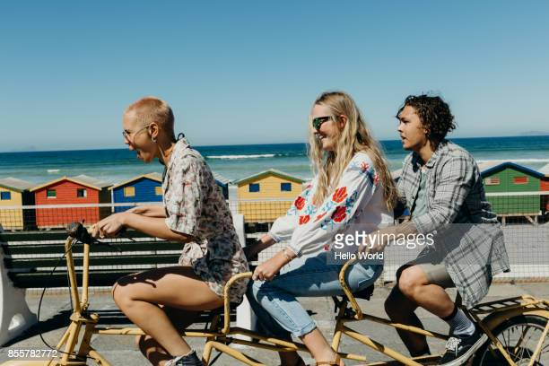 three friends laughing on a tandem bicycle on a boardwalk - three people stock pictures, royalty-free photos & images
