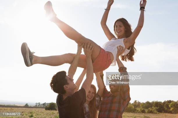three friends lifting young woman above their heads - picking up stock pictures, royalty-free photos & images