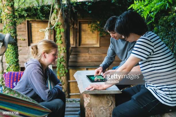 Três amigos, olhando para um tablet digital em um pátio.