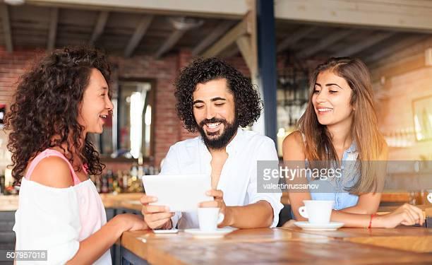 Trois amis regardant tablette numérique au bar