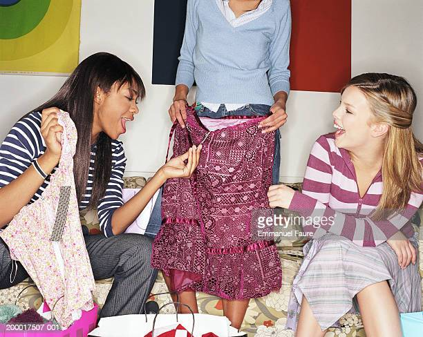 Three friends looking at newly purchased clothing