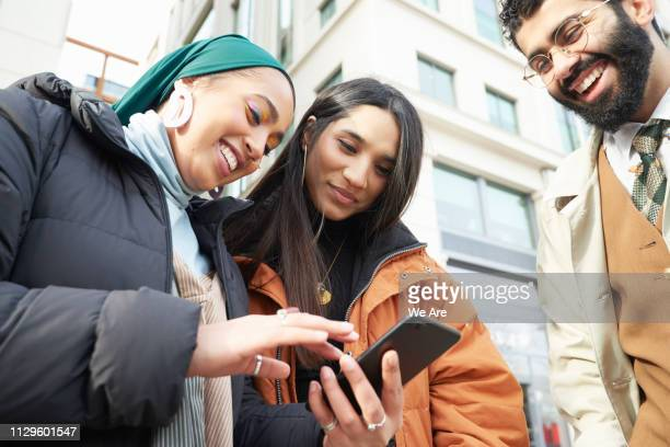 Three friends looking at smartphones.