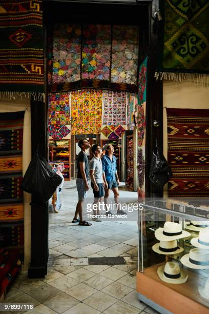 three friends looking at wall filled with blankets while shopping in local market - merida mexico stock photos and pictures