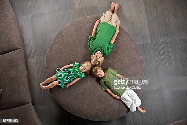 Three friends lying on a round sofa