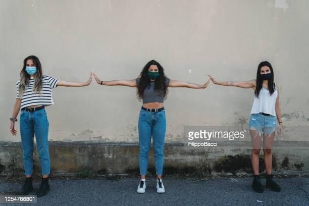 drie vrienden die veiligheidsafstand tegen een muur in de stad handhaven - menselijke ledematen stockfoto's en -beelden