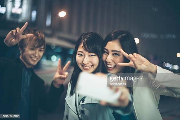 3 つの友人を自分撮り夜に通りに