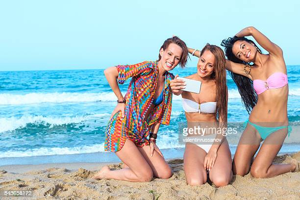 Three friends making selfie on the beach
