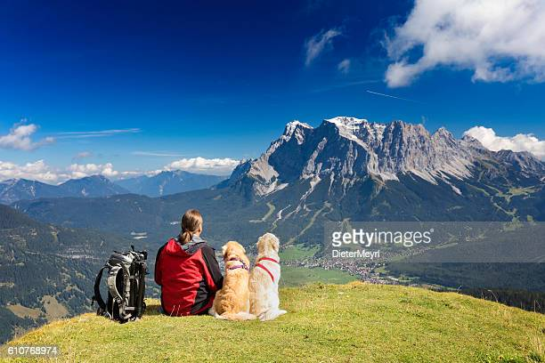 Three friends, man with  his dogs are looking to Zugspitze