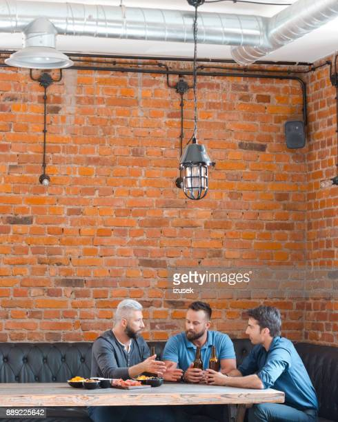 Three friends meeting at pub after work