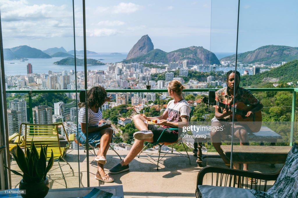 Drie vrienden op het balkon met uitzicht op de berg sugarloaf : Stockfoto