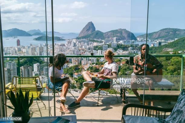 three friends on balcony with views of sugarloaf mountain - rio de janeiro imagens e fotografias de stock