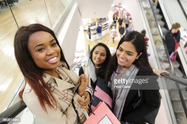 Three friends on escalator in shop