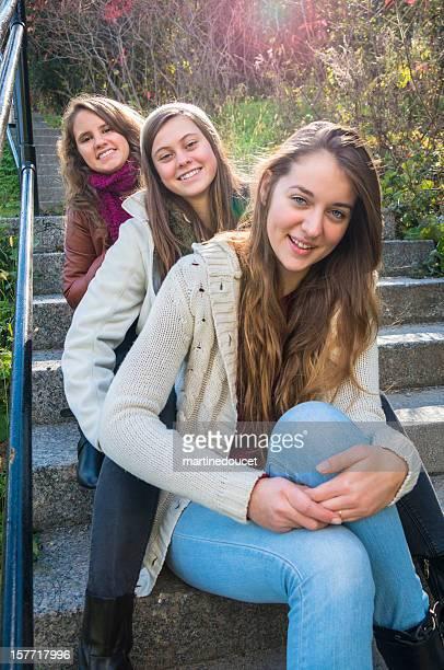 Drei Freunde auf der Treppe außerhalb, vertikal.