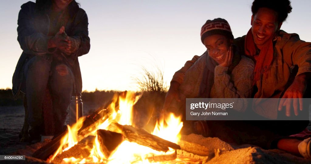 Three friends on the beach watching the flames of the camp fire. : ストックフォト