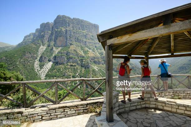 three friends overlooking vikos canyon, deepest gorge in europe, zagoria / epirus, greece - epirus greece stock pictures, royalty-free photos & images