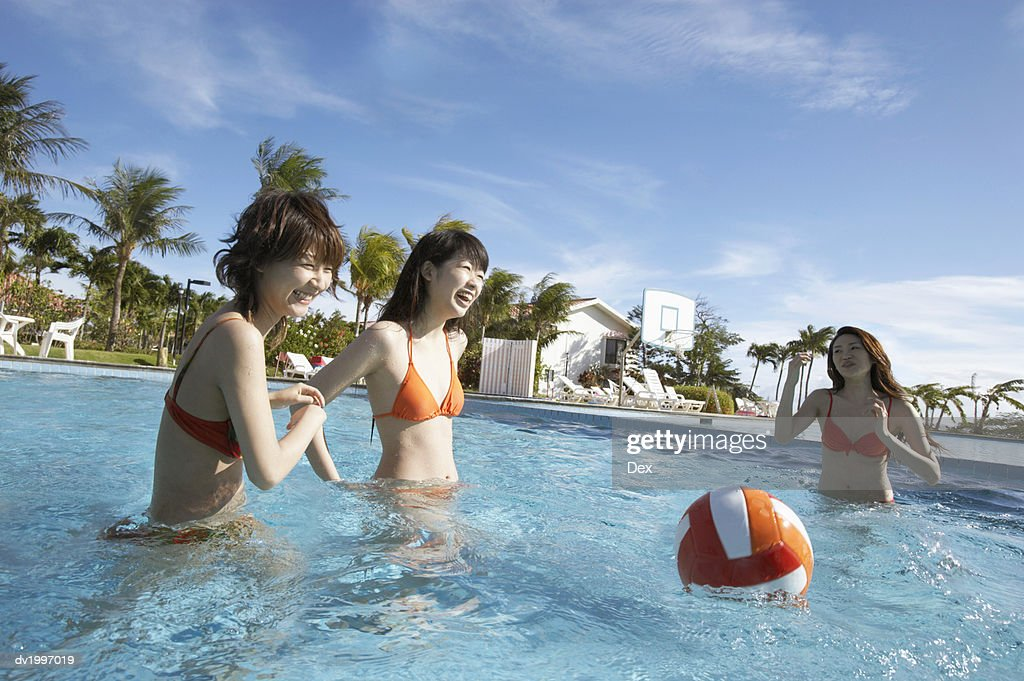 Three Friends Playing in a Swimming Pool : Stock Photo