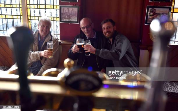 Three friends pose for the photographer inside the Cornucopia pub on May 17, 2021 in Southend, England. From today, pandemic-inspired restrictions on...