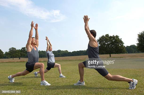 Three friends practising yoga in park