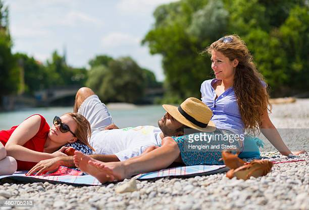 Three friends relaxing by Isar River, Munich, Germany