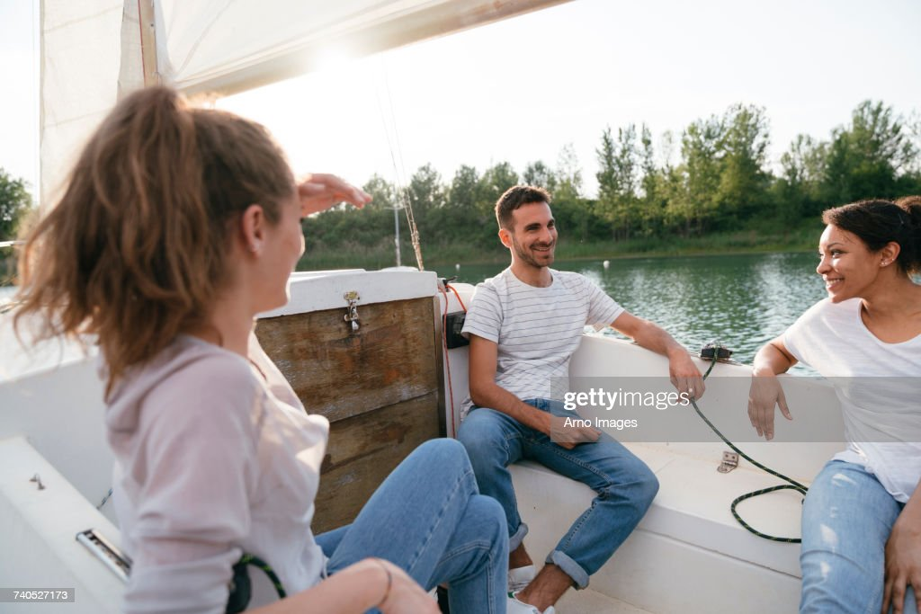 Three friends relaxing on sailing boat on lake : Stock Photo