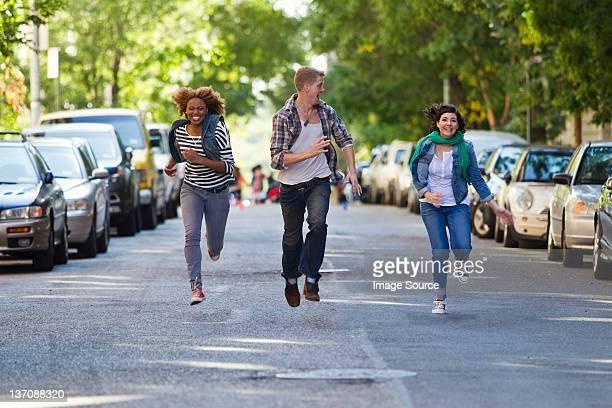 Three friends running through city street