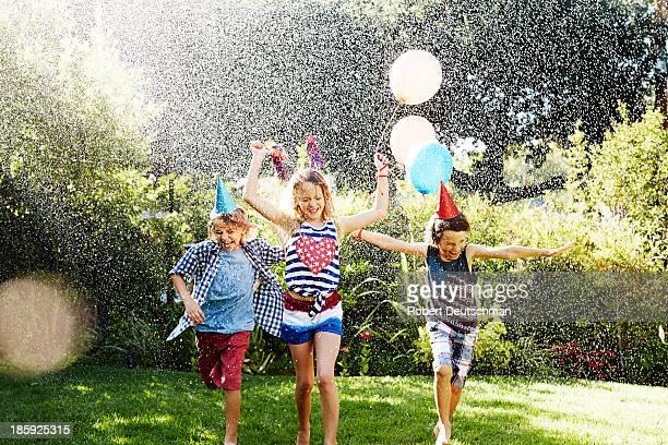 Three friends running through water drops.