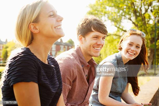 Three friends sat on wall laughing.